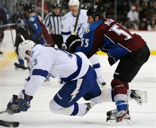 Colorado Avalanche left wing Cody McLeod, right, checks Tampa Bay Lightning defenseman Pavel Kubina, left, of the Czech Republic, in the first period of an NHL hockey game on Friday, Dec. 23, 2011, in Denver. (AP Photo/Chris Schneider)