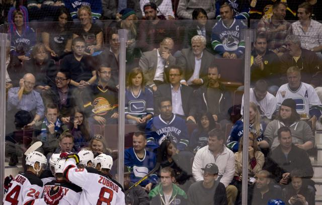 Vancouver Canucks fans sit and watch as New Jersey Devils right wing Jaromir Jagr (68) is congratulated on his goal during the first period of an NHL hockey game Tuesday, Oct. 8, 2013, in Vancouver, British Columbia. (AP Photo/The Canadian Press, Jonathan Hayward)
