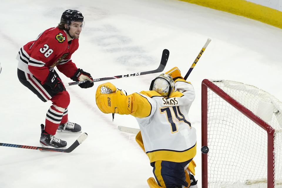 Chicago Blackhawks' Brandon Hagel (38) scores against Nashville Predators goaltender Juuse Saros during overtime in an NHL hockey game Wednesday, April 21, 2021, in Chicago. The Blackhawks won 5-4. (AP Photo/Charles Rex Arbogast)