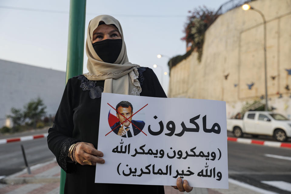An Arab Israeli Muslim demonstrator, clad in mask due to the COVID-19 coronavirus pandemic, holds up a sign during a rally protesting against the comments of French President Emmanuel Macron over Prophet Mohammed cartoons, in the Arab town of Umm-Al Fahem in Northen Israel on October 25, 2020. (Photo by Ahmad GHARABLI / AFP) (Photo by AHMAD GHARABLI/AFP via Getty Images)
