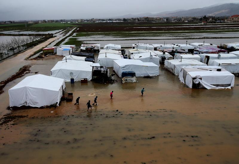 FILE - In this Tuesday Jan. 8, 2013 file photo, Syrian refugees make their way in flooded water at a temporary refugee camp, in the eastern Lebanese Town of Al-Faour near the border with Syria, Lebanon. International aid officials are framing a new appeal for help in easing Syria's humanitarian crisis in terms not seen since the height of the Iraq war: Refugee numbers possibly swelling toward 1 million and more than double that figure in need of help inside the country. (AP Photo/Hussein Malla, File)