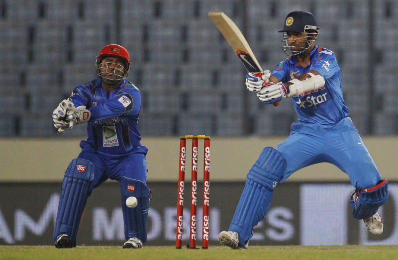 India's Ajinkya Rahane, right, plays a shot as Afghanistan's Mohammad Shahzad watches during their match in the Asia Cup one-day international cricket tournament in Dhaka, Bangladesh, Wednesday, March 5, 2014. (AP Photo/A.M. Ahad)