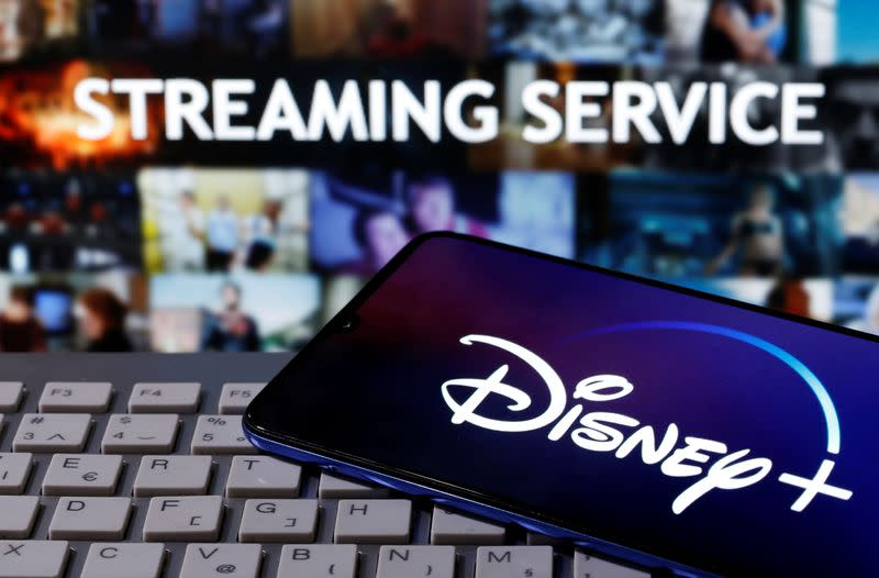 """Smartphone with displayed """"Disney"""" logo is seen on the keyboard in front of displayed """"Streaming service"""" words in this illustration"""