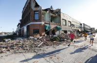<p>A local resident runs past a tornado-damaged building on Main Street, Thursday, July 19, 2018, in Marshalltown, Iowa. Several buildings were damaged by a tornado in the main business district in town including the historic courthouse. (Photo: Charlie Neibergall/AP) </p>