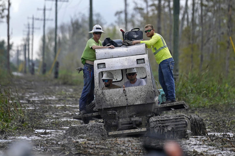 Electrical workers ride through marsh in a marsh buggy to restore power lines in the aftermath of Hurricane Ida in Houma, La., Friday, Sept. 17, 2021. The Louisiana terrain presents special challenges like just getting out to some of the areas where power poles and lines need to be fixed. In some areas lines thread through thick swamps that can only be accessed by air boat or specialized equipment like a marsh buggy. Linemen don waders to climb into chest-high muddy waters also home to alligators and water moccasins. (AP Photo/Gerald Herbert)