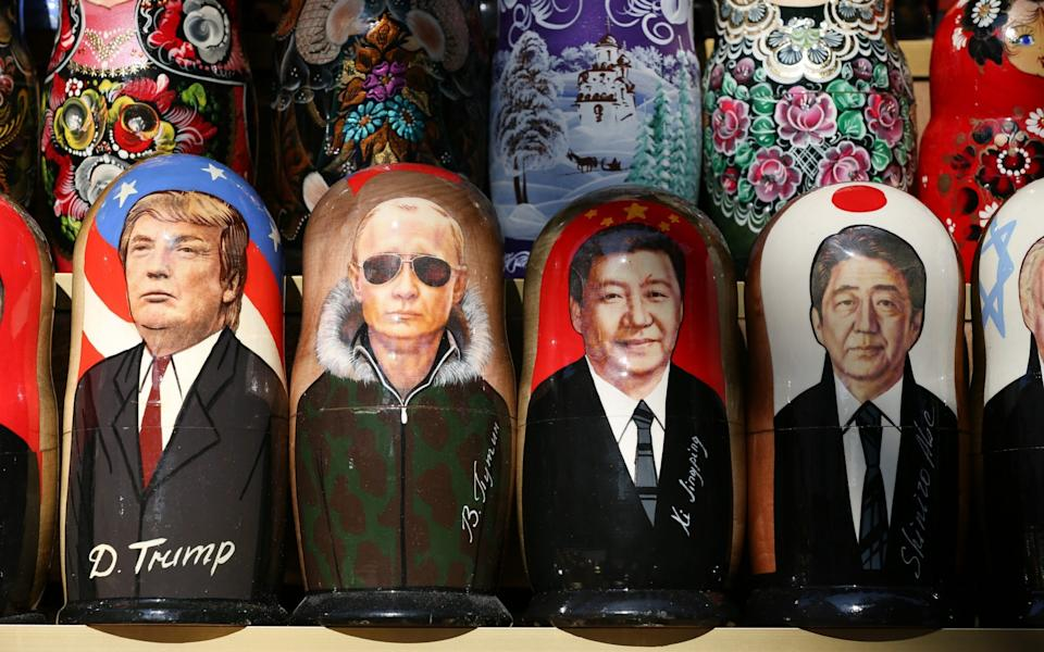 President Trump - here on a matryoshka doll in St Petersburg with other global leaders - wanted to use aid to counter China's growing influence  - Bloomberg
