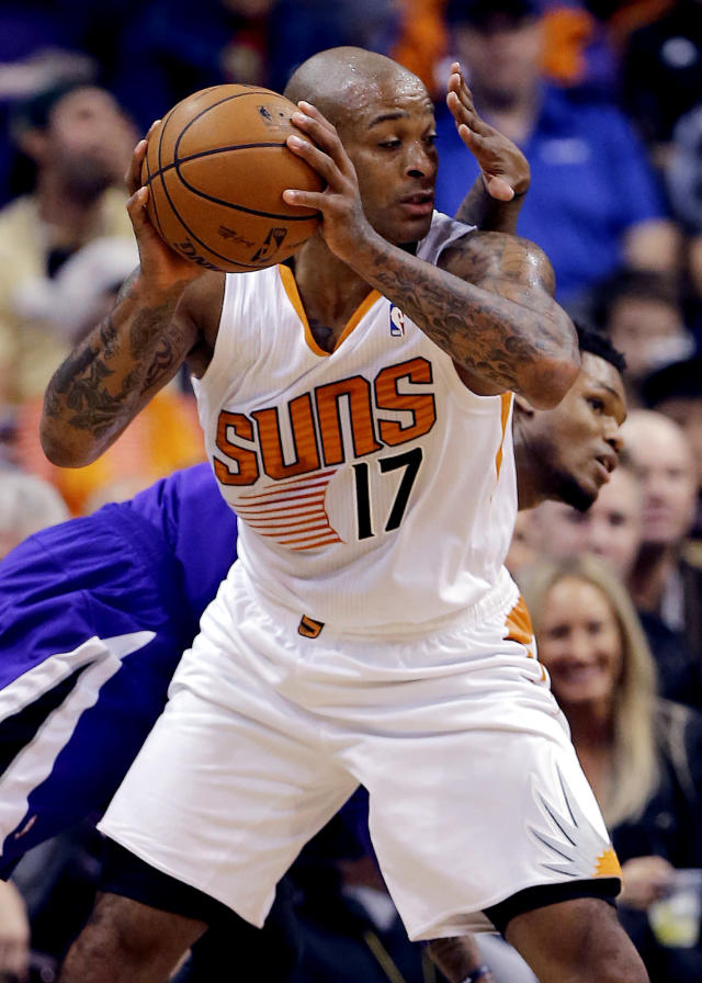 Sacramento Kings' DeMarcus Cousins gets a hand in the face of Phoenix Suns' P.J. Tucker (17) during the first half of an NBA basketball game on Friday, Dec. 13, 2013, in Phoenix. (AP Photo/Matt York)