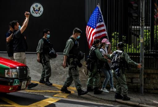 Police remove a woman holding a US flag from outside the US consulate in Hong Kong on July 4