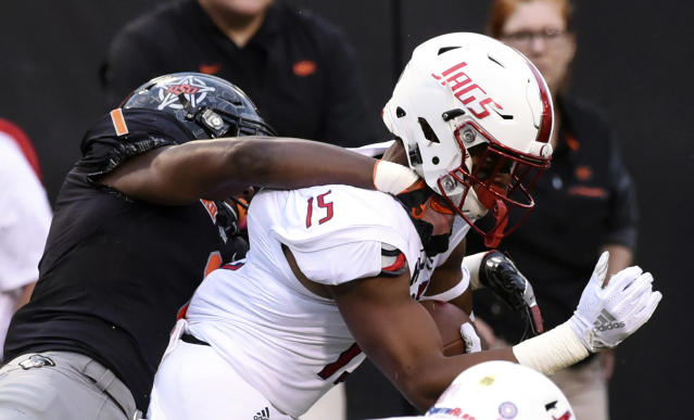 South Alabama wide receiver Kawaan Baker (15) is tackled by Oklahoma State linebacker Calvin Bundage (1) during an NCAA college football game in Stillwater, Okla., Saturday, Sept. 8, 2018. (AP Photo/Brody Schmidt)