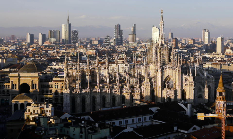 FILE - In this Jan. 4, 2017 file photo, the pinnacles of the Duomo gothic cathedral are illuminated by the afternoon sun and backdropped by the new business district, in Milan, northern Italy. A wide swath of northern Italy will benefit from 1 billion euros ($1.2 billion) in infrastructure development that the government has signed off on to improve access to the venues for the Milan-Cortina Winter Olympics in 2026. The funds are destined for road and railway projects in the Lombardy and Veneto regions and the Bolzano and Trento provinces that will host the games. (AP Photo/Luca Bruno, File)