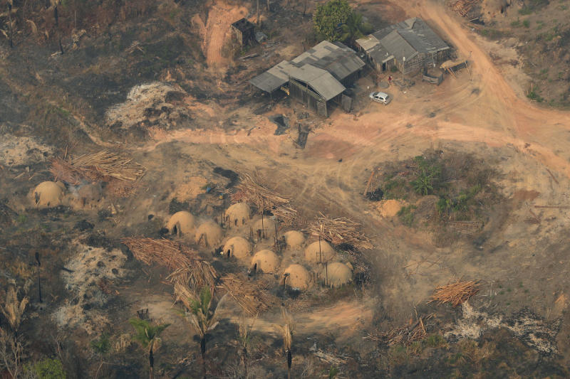 Charcoal-making furnaces and wooden planks are seen from the air, in the city of Jaci Parana, Rondonia state, Brazil, Saturday, Aug. 24, 2019. Brazil says military aircraft and 44,000 troops will be available to fight fires sweeping through parts of the Amazon region. The defense and environment ministers have outlined plans to battle the blazes that have prompted an international outcry as well as demonstrations in Brazil against President Jair Bolsonaro's handling of the environmental crisis. (AP Photo/Eraldo Peres)
