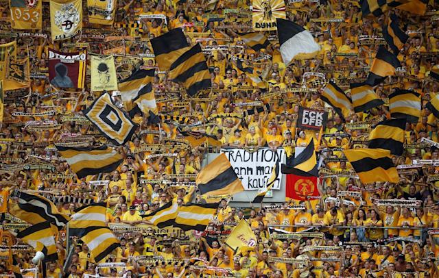 Football Soccer - Dynamo Dresden v RB Leipzig - German Cup (DFB Pokal) - DDV-Stadion, Dresden, Germany - 20/08/16. Dynamo Dresden's fans display banners and wave flags. REUTERS/Axel Schmidt DFB RULES PROHIBIT USE IN MMS SERVICES VIA HANDHELD DEVICES UNTIL TWO HOURS AFTER A MATCH AND ANY USAGE ON INTERNET OR ONLINE MEDIA SIMULATING VIDEO FOOTAGE DURING THE MATCH.