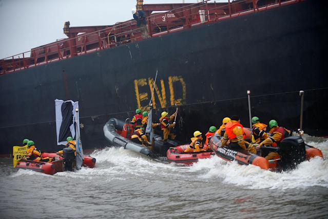 <p>Greenpeace activists write beside a banner with a silhouette of German Chancellor Angela Merkel onto the Golden Opportunity ship carrying coal as part of protests ahead of the upcoming G20 summit, in Hamburg Harbour, Germany July 2, 2017. (Hannibal Hanschke/Reuters) </p>