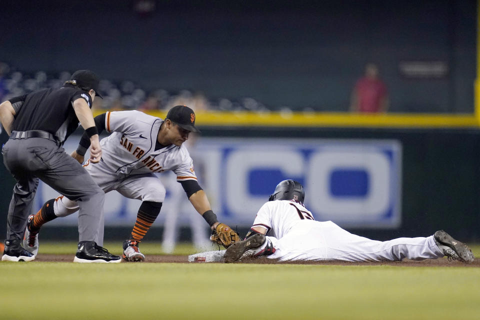 Arizona Diamondbacks' Nick Ahmed, right, slides safely into second base with a double as San Francisco Giants second baseman Donovan Solano, middle, applies a late tag while umpire Chris Guccione, left, looks on during the first inning of a baseball game, Thursday, Aug. 5, 2021, in Phoenix. (AP Photo/Ross D. Franklin)
