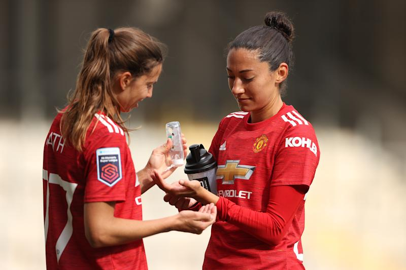 LEIGH, ENGLAND - OCTOBER 04: Tobin Heath of Manchester United Women applies hand sanitiser to the hands of Christen Press of Manchester United Women during the Barclays FA Women's Super League between Manchester United Women and Brighton & Hove Albion Women at Leigh Sports Village on October 4, 2020 in Leigh, England. (Photo by Matthew Ashton - AMA/Getty Images)