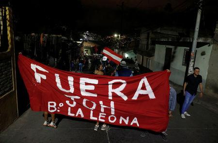 People hold up a banner at a protest during curfew, while the country is still mired in chaos over a contested presidential election, in Tegucigalpa