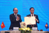 Vietnamese Prime Minister Nguyen Xuan Phuc, left, applauds as Minister of Trade Tran Tuan Anh, right, holds up a signed document during a virtual signing ceremony of the Regional Comprehensive Economic Partnership, or RCEP, trade agreement in Hanoi, Vietnam on Sunday, Nov. 15, 2020. China and 14 other countries have agreed to set up the world's largest trading bloc, encompassing nearly a third of all economic activity, in a deal many in Asia are hoping will help hasten a recovery from the shocks of the pandemic. (AP Photo/Hau Dinh)