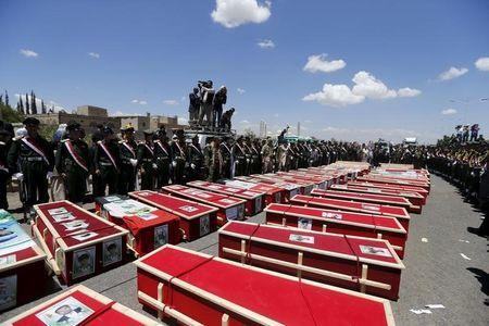 Police cadets gather around coffins of victims of suicide bombing attacks during a mass funeral procession in Sanaa March 25, 2015. REUTERS/Khaled Abdullah
