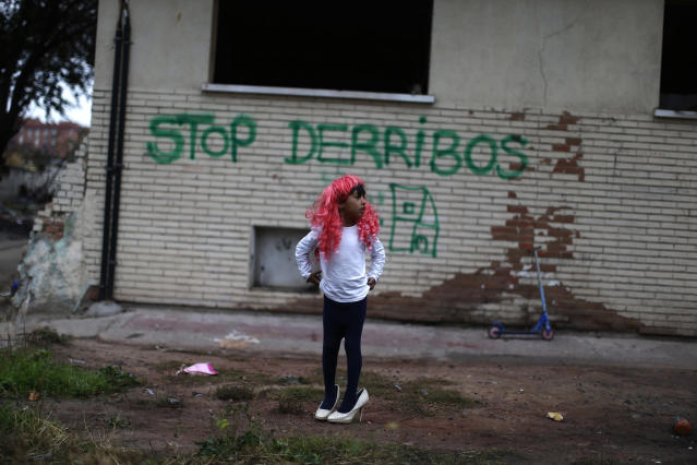 <p>Antonio Acuna, 10, wearing a wig and high-heeled shoes, stands on the street during the postponement of his family's eviction and demolition of their house in Madrid, Nov. 7, 2013. (AP Photo/Andres Kudacki) </p>