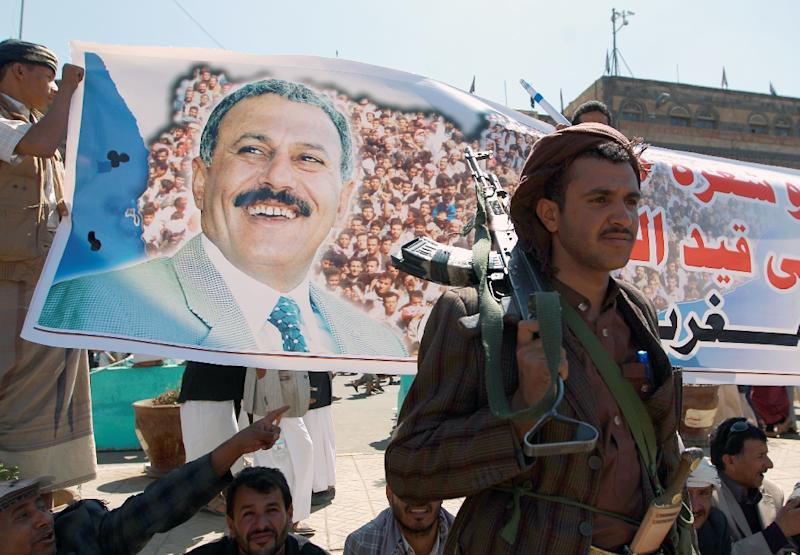 Gunmen loyal to Yemen's former president Ali Abdullah Saleh (on poster) take part in a rally in the capital Sanaa to protest threatened UN sanctions against the ousted strongman and insurgent chiefs on November 7, 2014 (AFP Photo/Mohammed Huwais)
