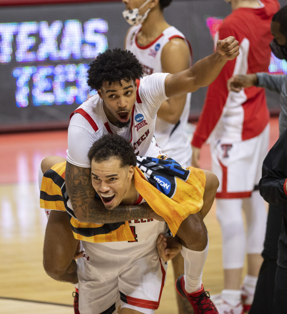 Texas Tech guard Kyler Edwards (11) catches a ride on the back of teammate forward Marcus Santos-Silva (14) as the two celebrate their win over Utah State in a first round game in the NCAA men's college basketball tournament, Friday, March 19, 2021, at Assembly Hall in Bloomington, Ind. (AP Photo/Doug McSchooler)