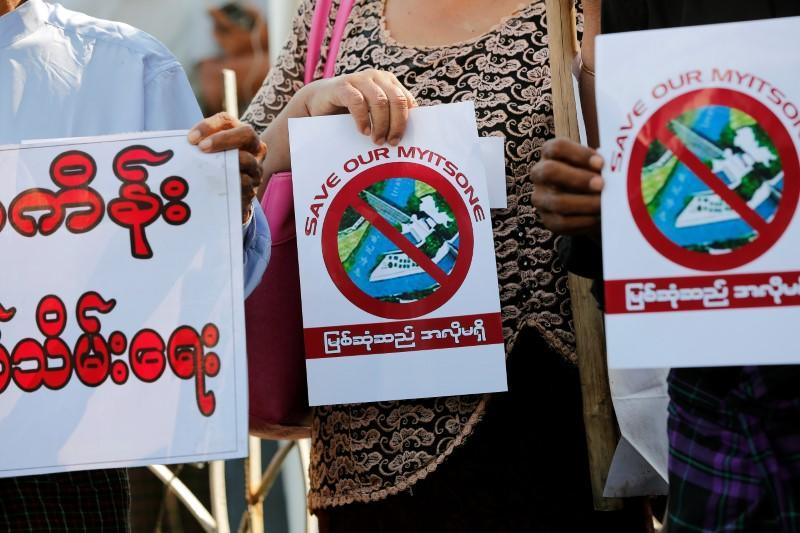 Protesters hold flyers against Myitsone hydropower dam during the last day of Chinese President Xi Jinping's visit in Yangon