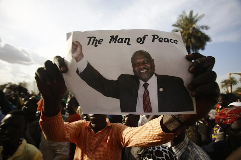 A man holds a picture of South Sudanese rebel leader Riek Machar