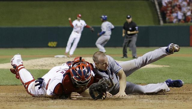 St. Louis Cardinals catcher Yadier Molina tags out Los Angeles Dodgers' Mark Ellis at home during the 10th inning of Game 1 of the National League baseball championship series Friday, Oct. 11, 2013, in St. Louis. (AP Photo/David J. Phillip)
