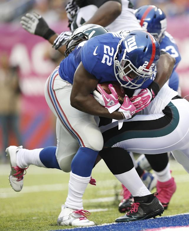 New York Giants' David Wilson (22) breaks a tackle by Philadelphia Eagles' DeMeco Ryans for a touchdown during the first half of an NFL football game Sunday, Oct. 6, 2013, in East Rutherford, N.J. (AP Photo/Kathy Willens)