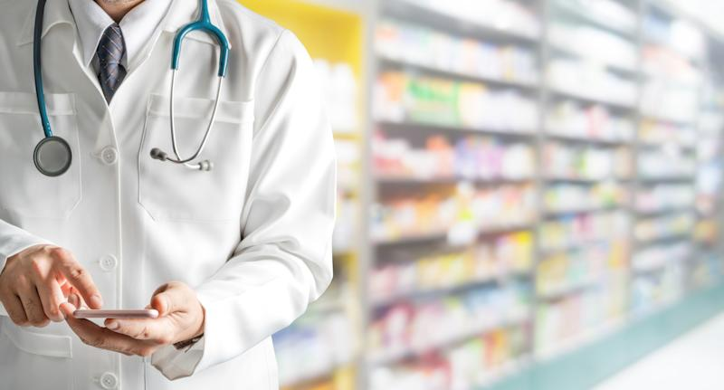 Pharmacist holding phone with drug shelves in background