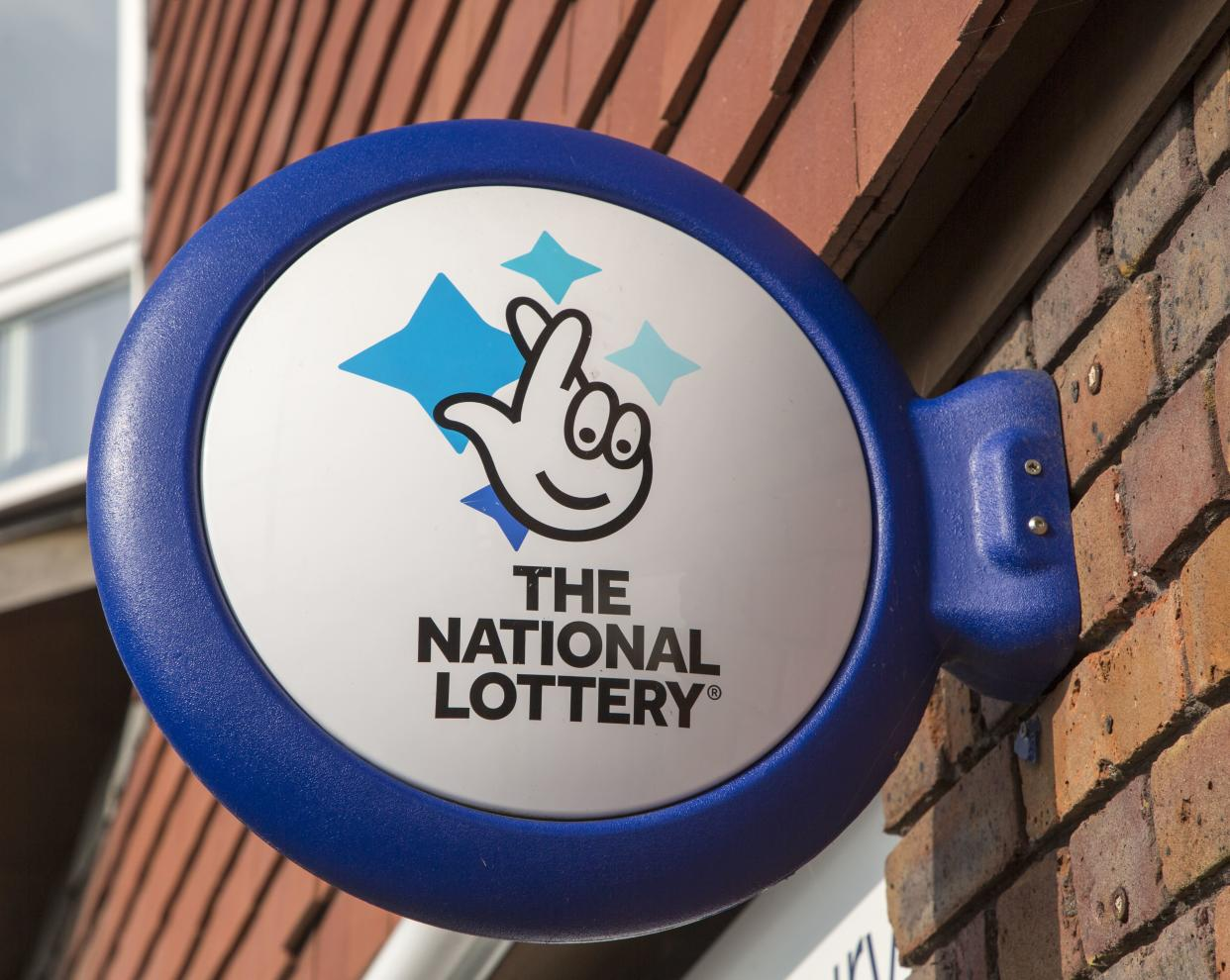 Wall mounted sign for the National Lottery, Amesbury, Wiltshire, England, UK. (Photo by: Geography Photos/Universal Images Group via Getty Images)