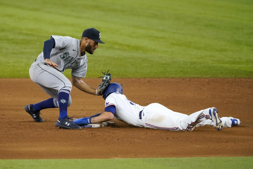 Seattle Mariners second baseman Abraham Toro attempts the tag on Texas Rangers' Eli White, who stole second during the fifth inning of a baseball game in Arlington, Texas, Saturday, July 31, 2021. (AP Photo/Tony Gutierrez)