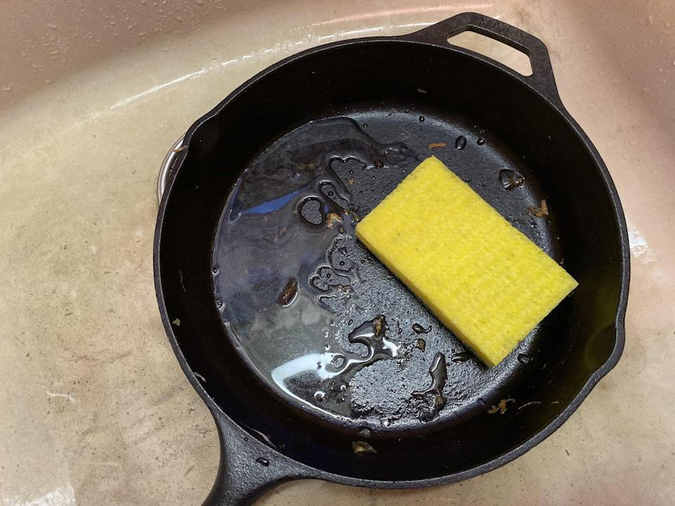 <p>Put the skillet in your sink and put some hot water on the cooking surface. Use the sponge to loosen up any burnt-on bits and get any excess oil or spices off of the skillet. Do not use soap on a cast iron skillet because it may strip away the seasoning.</p>