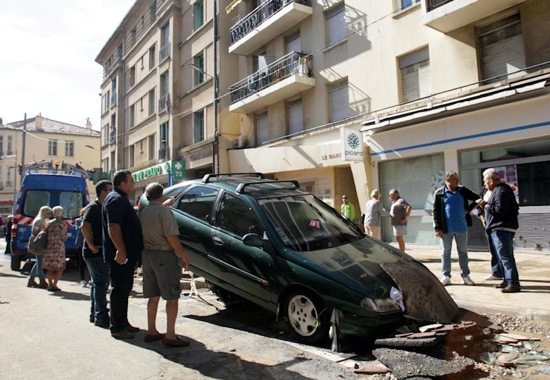 People stand in front of a damaged car in downtown Cannes, southeastern France, on October 4, 2015 (AFP Photo/Patrick Clemente)