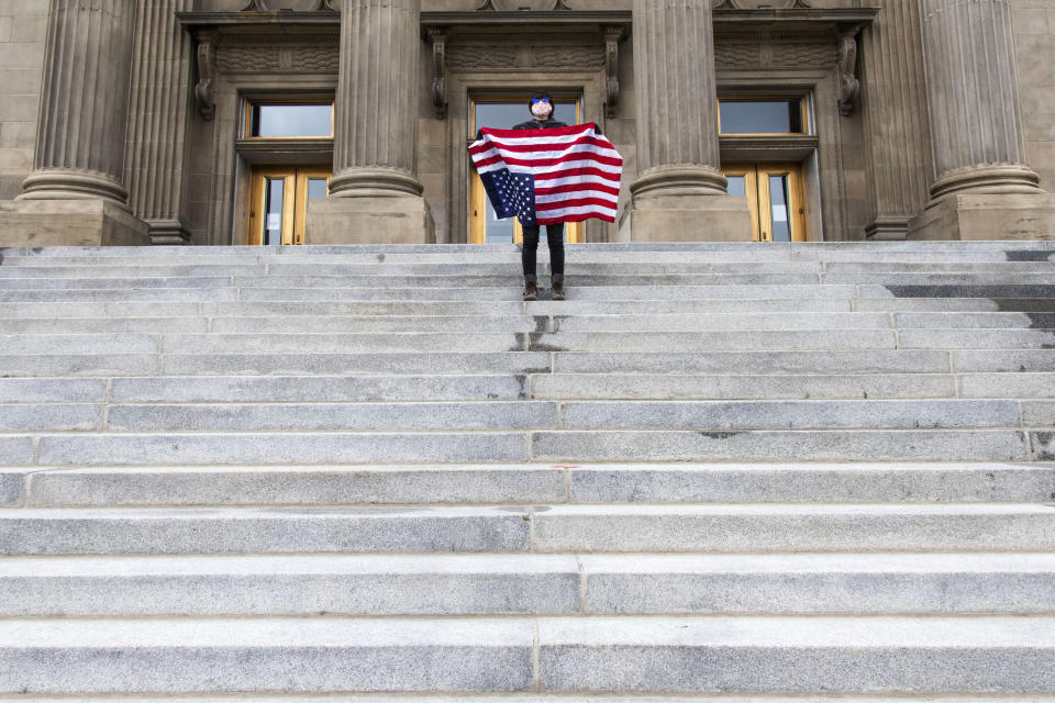 """FILE - In this April 26, 2021, file photo, a student holding a U.S. flag upside down stands atop the steps at the Idaho Capitol building in Boise. The Idaho Senate has approved legislation aimed at preventing schools and universities from """"indoctrinating"""" students through teaching critical race theory, which examines the ways in which race and racism influence American politics, culture and the law. (Darin Oswald/Idaho Statesman via AP, File)"""