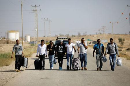 African migrants walk on a road after being released from Saharonim Prison in the Negev desert