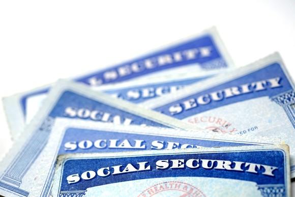 A small stack of Social Security cards messily laid on top of each other.