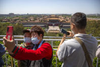 Visitors wearing face masks pose for a selfie at a viewing area overlooking the Forbidden City at a public park in Beijing, Saturday, May 1, 2021. Chinese tourists are expected to make a total of 18.3 million railway passenger trips on the first day of the country's five-day holiday for international labor day, according to an estimate by the state railway group, as tourists rush to travel domestically after the coronavirus has been brought under control in China. (AP Photo/Mark Schiefelbein)