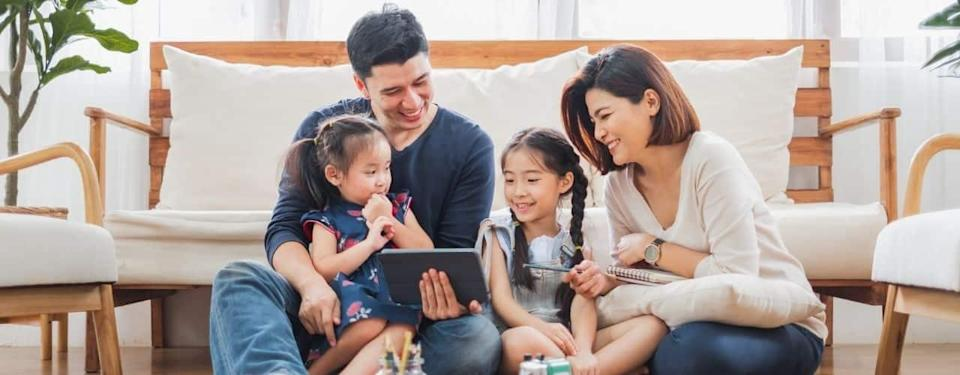 family using tablet, laptop for playing game watching movies, relaxing at home