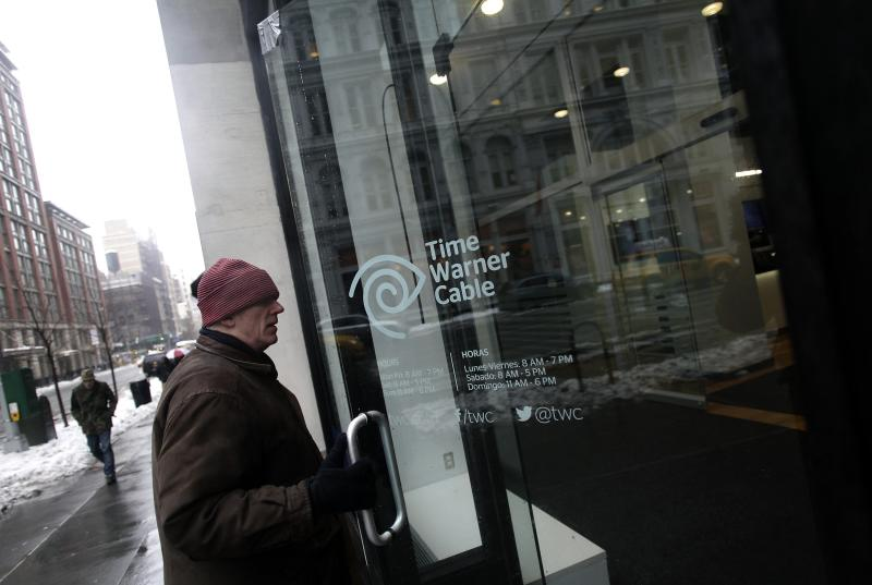 A man enters the Time Warner Cable headquarters in New York