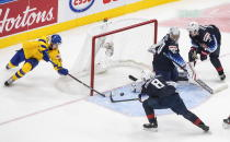 Sweden's Albin Sundsvik (29) tries to knock in the loose puck as U.S. goalie Spencer Knight (30) makes the stop and Jake Sanderson (8) and John Farinacci (25) defend during the second period of an IIHF World Junior Hockey Championship game Thursday, Dec. 31, 2020, in Edmonton, Alberta. (Jason Franson/The Canadian Press via AP)