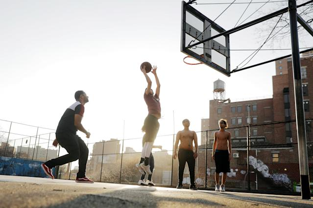 A group of young men play basketball on an outdoor court on a day of unseasonably warm weather in New York, U.S., February 21, 2018. REUTERS/Lucas Jackson