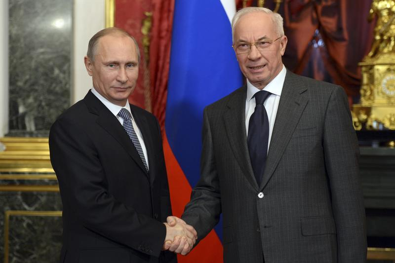 Russian President Vladimir Putin shakes hands with Ukrainian Prime Minister Mykola Azarov before a session of the Supreme Eurasian Economic Council at the Kremlin in Moscow