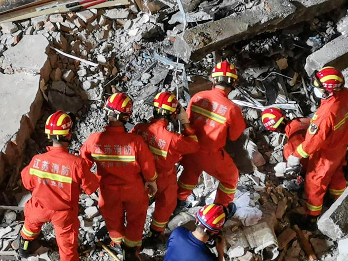 Rescuers searching at the site of a hotel after it collapsed leaving at least eight dead and nine others missing in the city of Suzhou in China's eastern Jiangsu province (AFP via Getty Images)