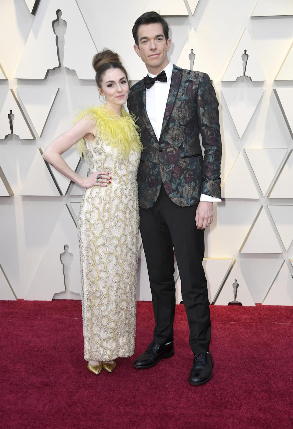 <p>Annamarie is wearing a feathered dress, and John is wearing a printed tuxedo.</p>