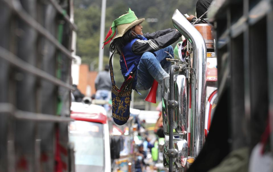 An Indigenous youth climbs the side of a bus during a national strike in Bogota, Colombia, Wednesday, Oct. 21, 2020. Workers' unions, university students, human rights defenders, and Indigenous communities held a day of protest in conjunction with a national strike across Colombia to protest against the assassinations of social leaders, in defense of the right to protest and to demand advances in health, income and employment. (AP Photo/Fernando Vergara)