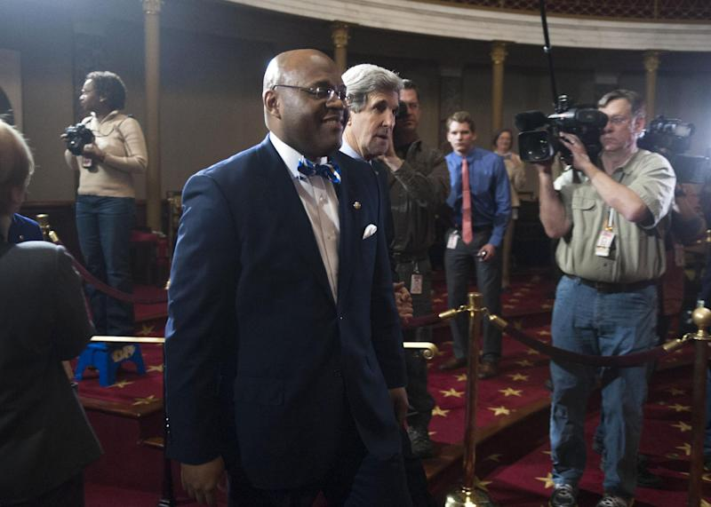 """Sen. William """"Mo"""" Cowan, D-Mass. walks into the Old Senate Chamber on Capitol Hill in Washington, Thursday, Feb. 7, 2013, with Secretary of State John Kerry, to take part in a re-enactment of the swearing-in as a Senator from Vice President Joe Biden . (AP Photo/Kevin Wolf)"""