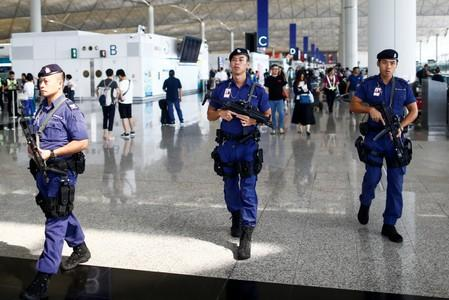 Armed police patrol the departure hall of the airport in Hong Kong after previous night's clashes with protesters