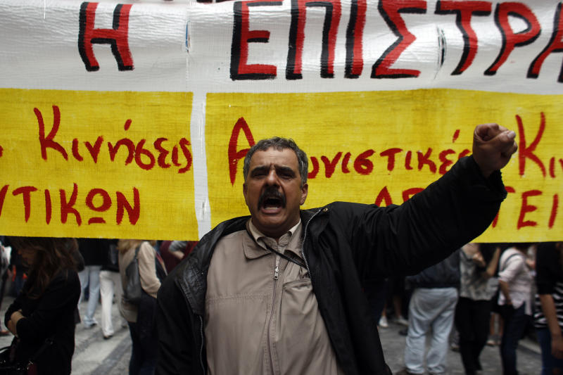 "A state school teacher  shouts slogans, in front of a banner that reads ""No to The Civil Mobilization"" during a peaceful protest in central Athens on Monday, May 13, 2013. Greece's conservative-led government has issued a civil mobilization order forcing state school teachers to work during university entrance exams later in May. Teachers' unions had been planning strikes during the exams, to protest planned increases in working hours and involuntary staff transfers _ as part of the financially-distressed country's austerity and reform program.  (AP Photo/Kostas Tsironis)"