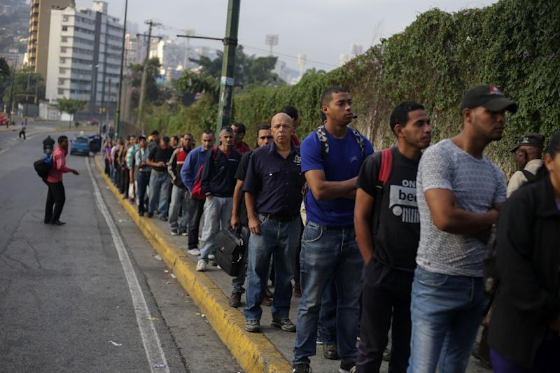 Many Venezuelans have been forced to walk very long distances during the power outage -- or face seemingly endless queues (AFP Photo/Cristian HERNANDEZ)